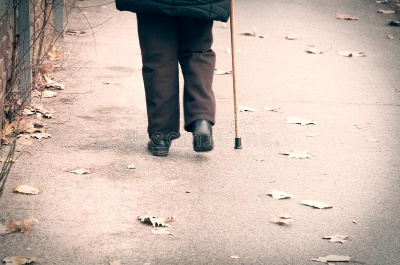 Old depressed woman walk alone down the street with walking stick or cane feeling lonely and lost view from back stock photography