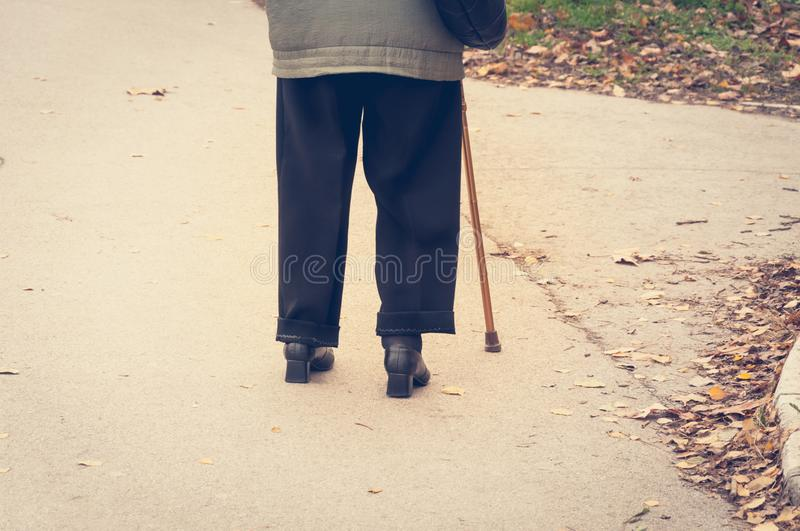 Old depressed woman walk alone down the street with walking stick or cane feeling lonely and lost view from back royalty free stock photo