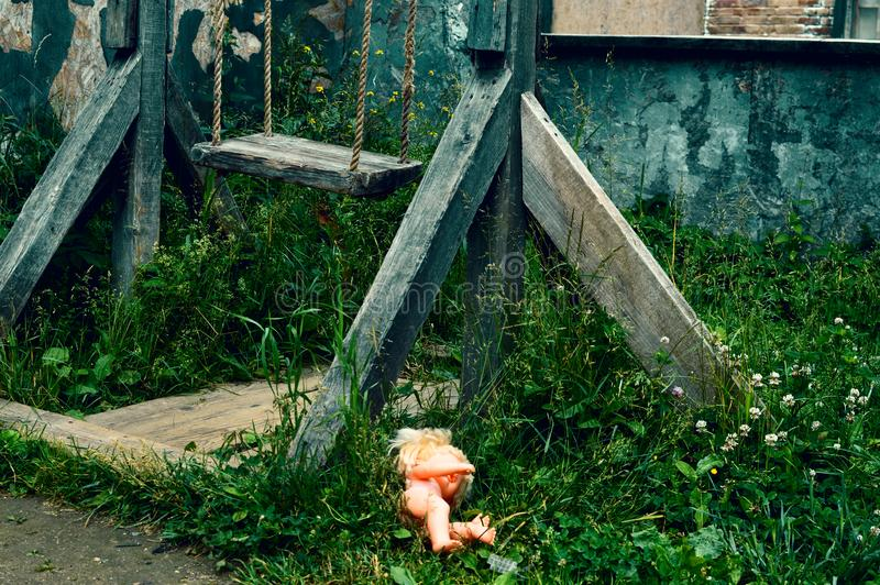 The old wooden broken swing. The forgotten plastic doll in a grass. royalty free stock image