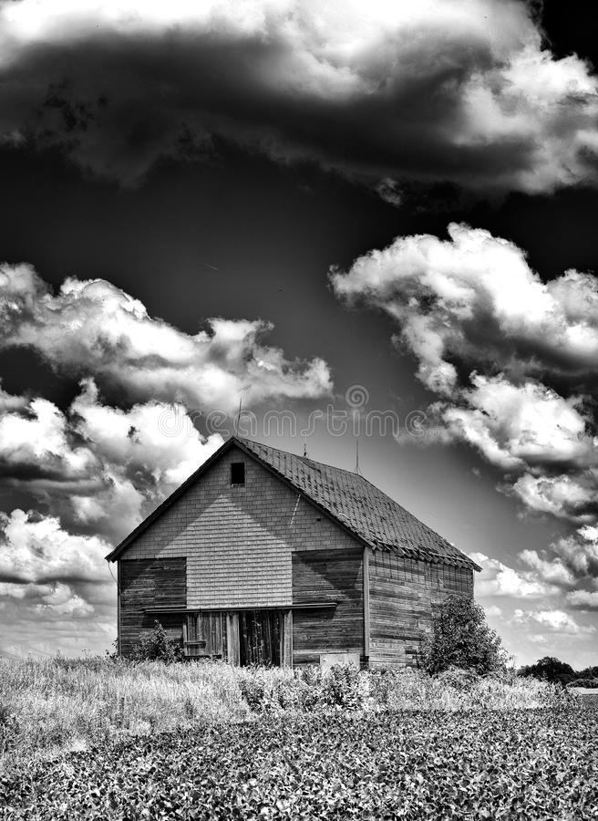 Old desolate barn with storm clouds overhead stock images