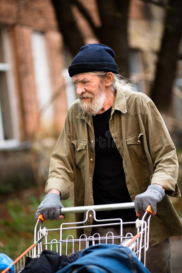 Old desperate tramp with stolen shopping cart. stock photo