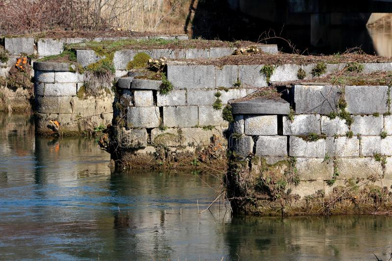 Old destroyed bridge rock and stone pylon foundation partially covered with dirt and moss surrounded with clear river stock images