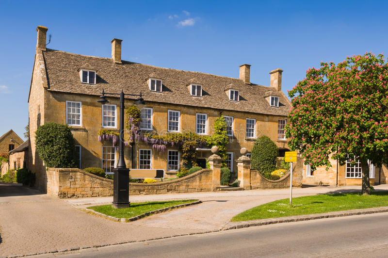 Old detached town house. With blossoming wisteria on the wall. Broadway high street. Cotswold country, Worcestershire, UK royalty free stock photo