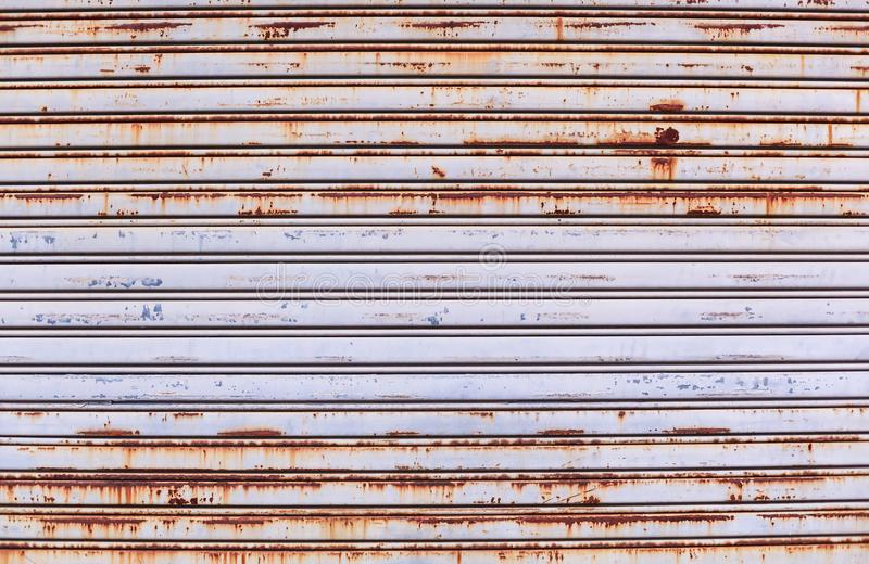 Old detailed aged vintage rusty textured zinc alloy metal roller shutter door, store front exterior design used in construction stock photography