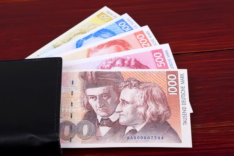 Old Deutsche Marks in the black wallet. On a wooden background royalty free stock images