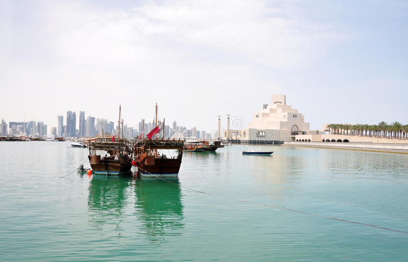 The old Dhow Harbor at the Doha Corniche, Qatar. A landscape of the Dhow Harbor in Doha, Qatar, with the Museum of Islamic Art, Dhow (old-style fishing boat) and royalty free stock images
