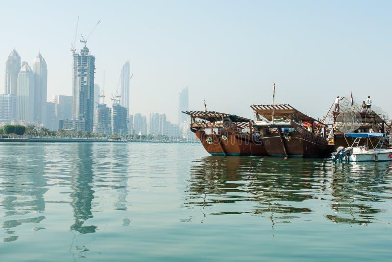 Old dhows alongside moderh highrise. Traditional Dhows tied up alongside modern high rise in central Abu Dhabi, UAE stock image