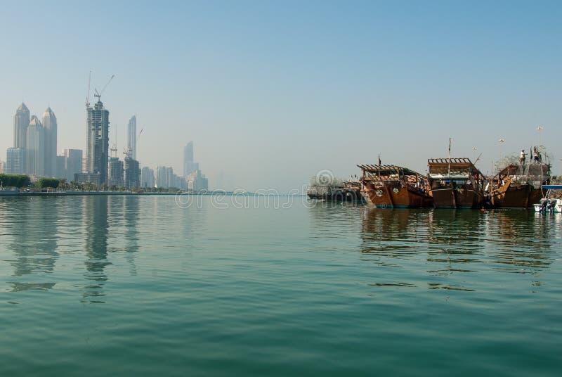 Old dhows alongside modern highrise. Traditional Dhows tied up alongside modern high rise in central Abu Dhabi, UAE royalty free stock image