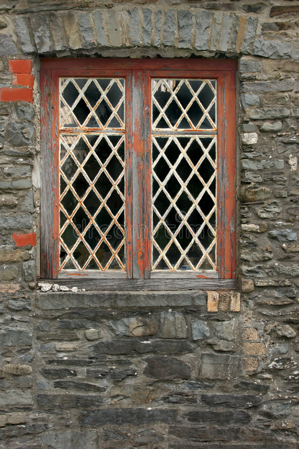 Old Diamond Leaded Windows. Old and dirty leaded diamond patterned windows set into an old stone wall royalty free stock photos