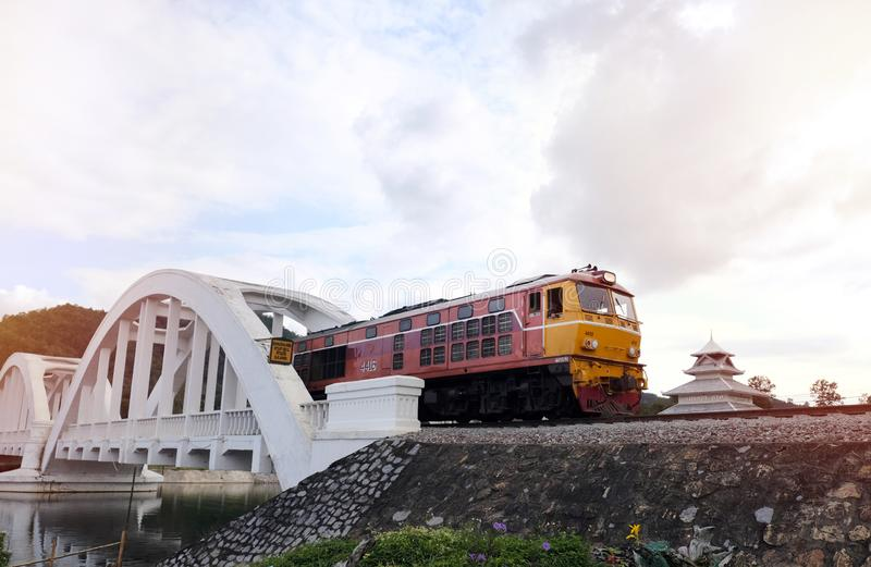 Old diesel train Running on the bridge over the white bridge The famous steel bridge in Lampoon, Thailand stock photo