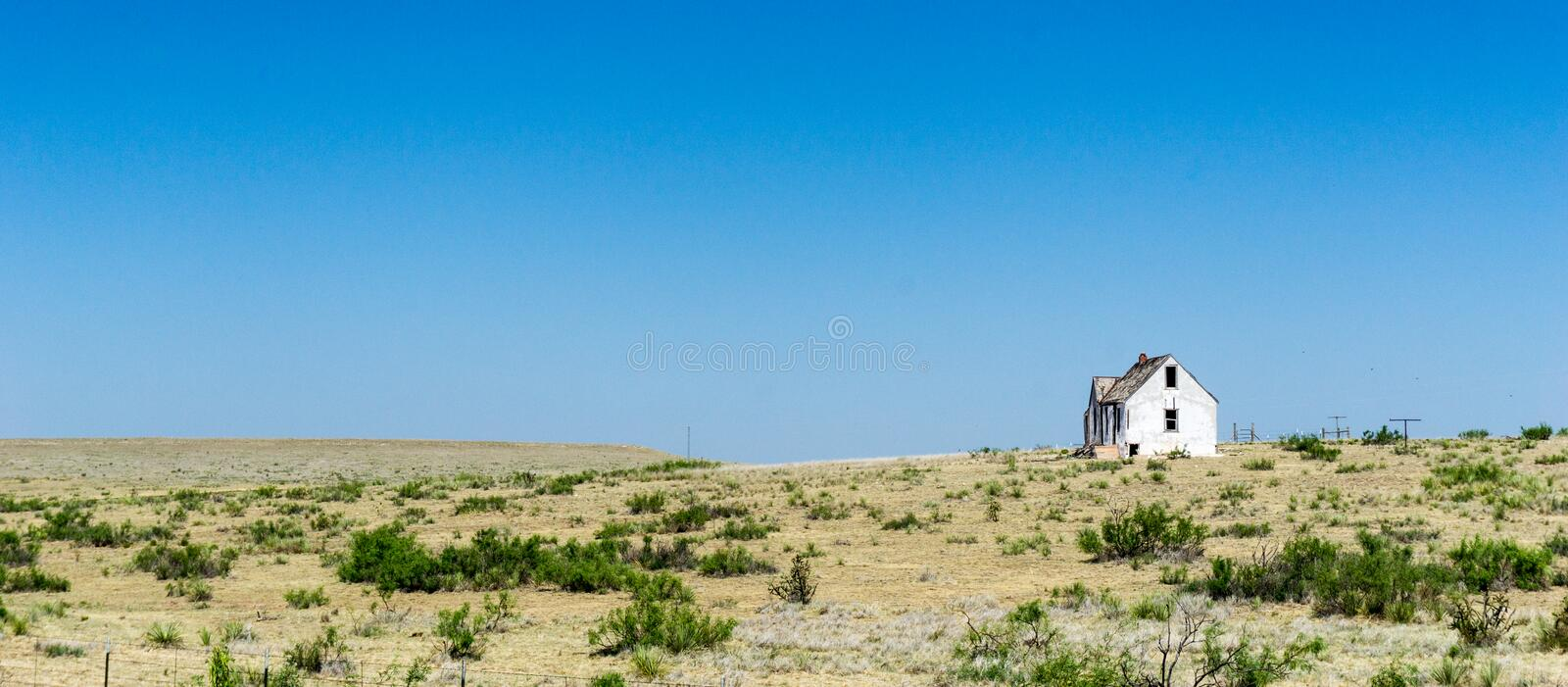Old dilapidated and abandoned white wooden house on the remote prairie in the middlew of nowhere under a blue sky royalty free stock images