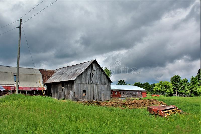 Old dilapidated farm located in Franklin County, upstate New York, United States. Abandoned dilapidated old wooden farm with surrounding green vegetation located stock photo