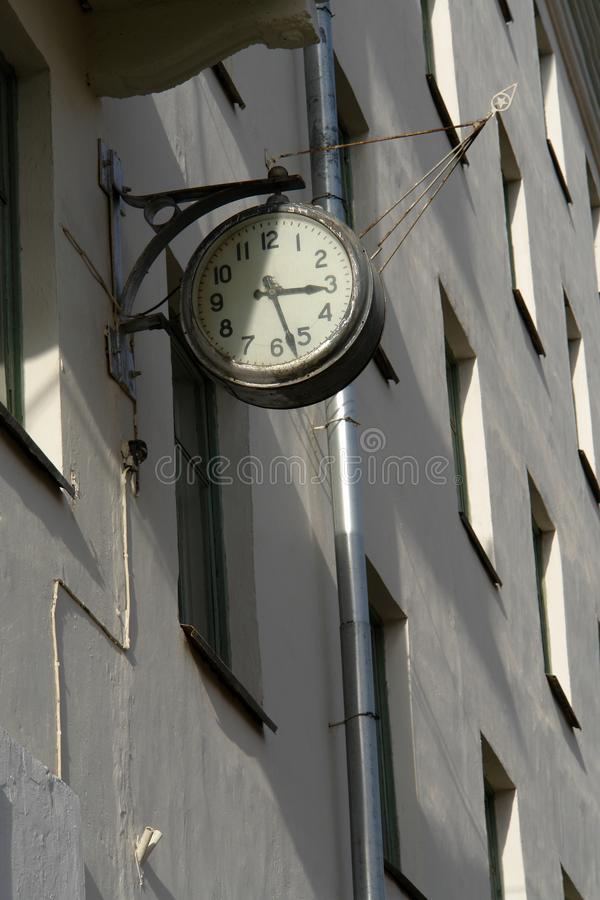 Old dilapidated gray street clock on wall of building. Shabby mechanical wall watch with scratches stock photos