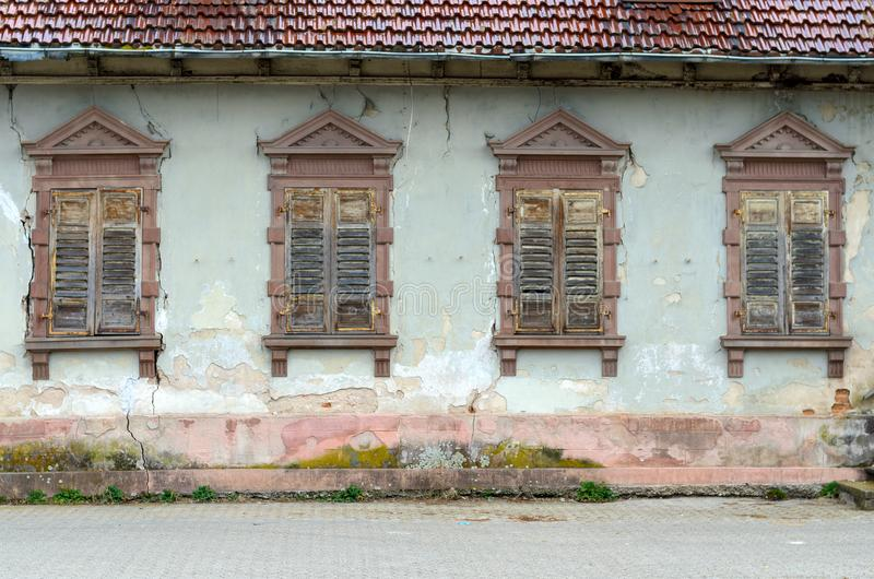 Dilapidated house with broken windows and shutters. Old dilapidated house with broken windows and shutters, a red tiled roof and grunge damaged wall with green royalty free stock image