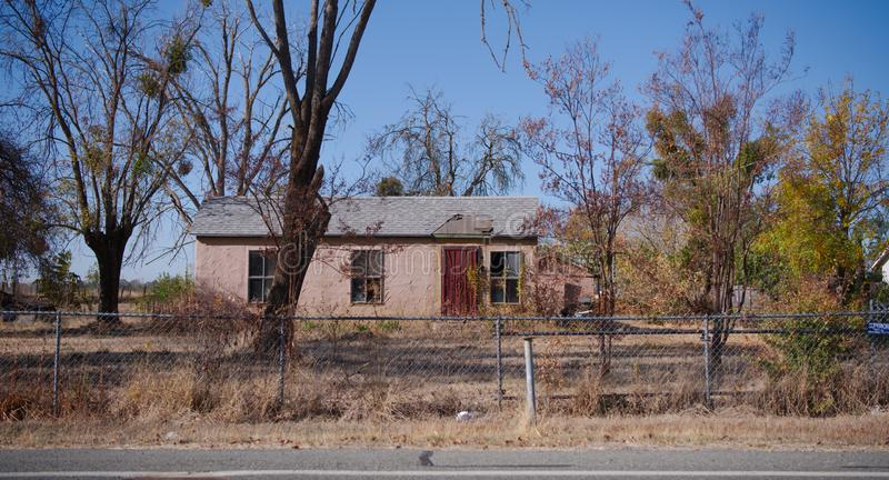 Old Dilapidated house by the road. An old dilapidated house by the side of the road. Unkept trees and weeds around yard royalty free stock photography