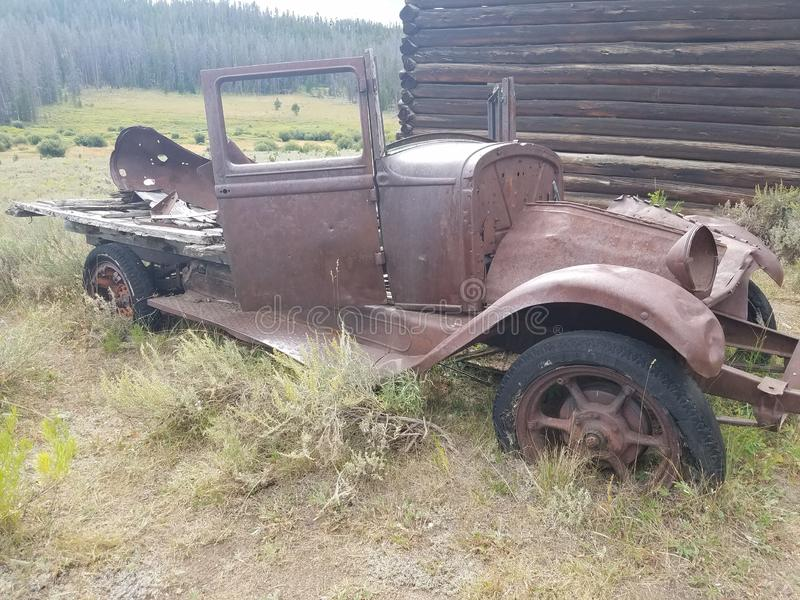 Old dilapidated 1920& x27;s roadster in front of a mining cabin. 1920s, rustic, centures, details, history, cars, autombile, antiques, forgotten stock photo