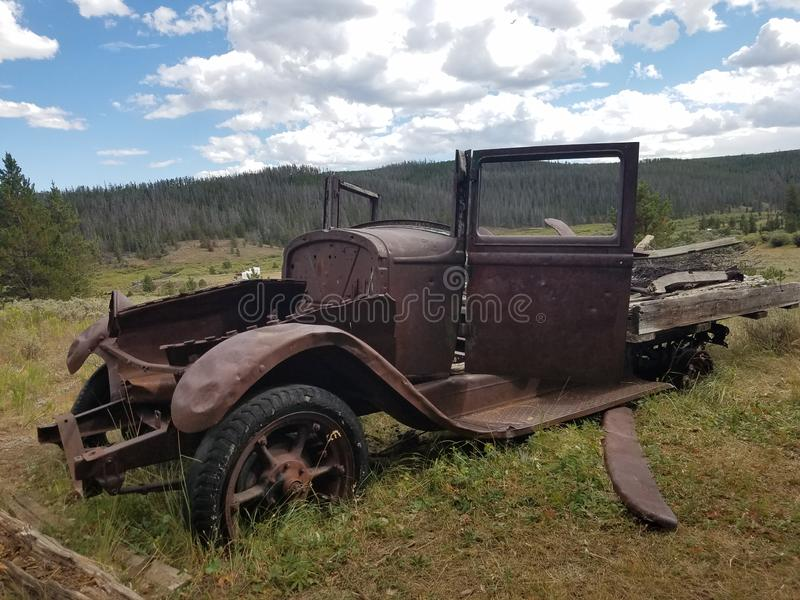 Old dilapidated 1920& x27;s roadster in front of a mining cabin. 1920s, rustic, centures, details, history, cars, autombile, antiques, forgotten royalty free stock photo