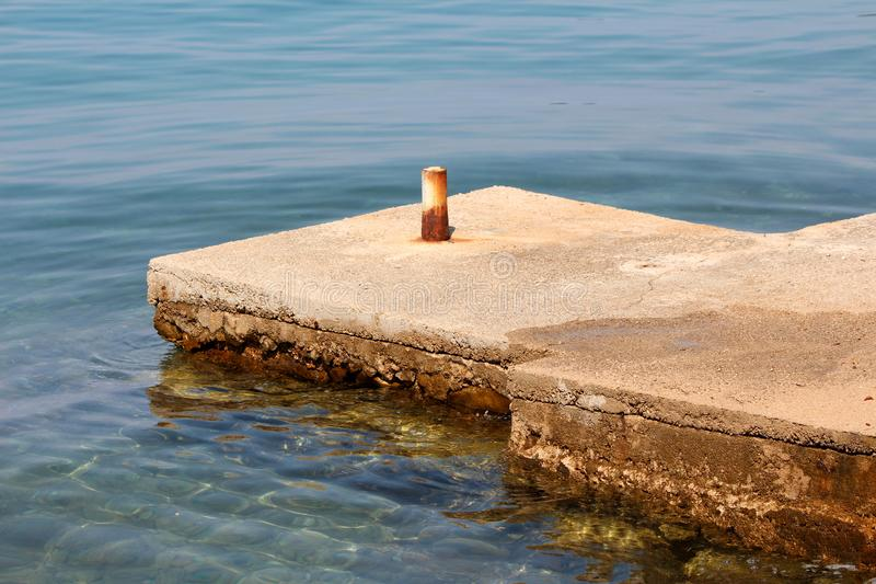 Old dilapidated stone and concrete local pier with strong rusted metal pipe used to tie boats surrounded with calm clear blue sea royalty free stock photos