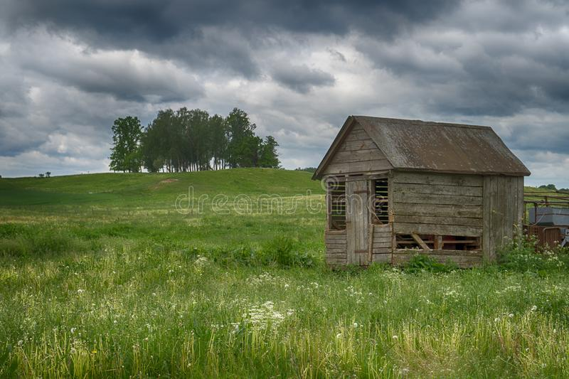 Old dilapidated wooden hut in a farm field stock photo