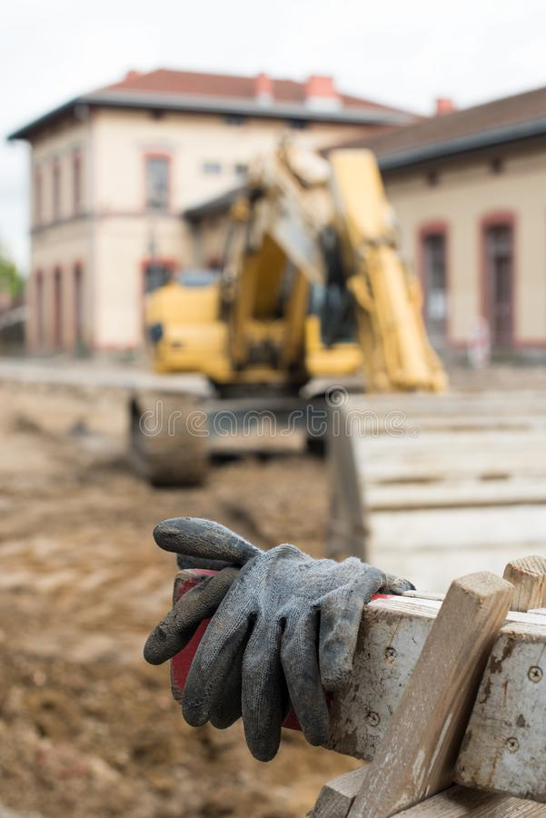 Old and dirty black gloves at construction site with big yellow digger in background stock photos