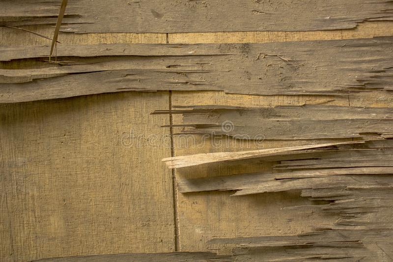 A old dirty broken light yellow plywood on a wooden surface. wooden texture royalty free stock image