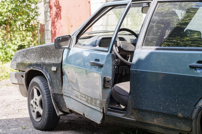 Old dirty car with open front door at the repair yard.  royalty free stock photo