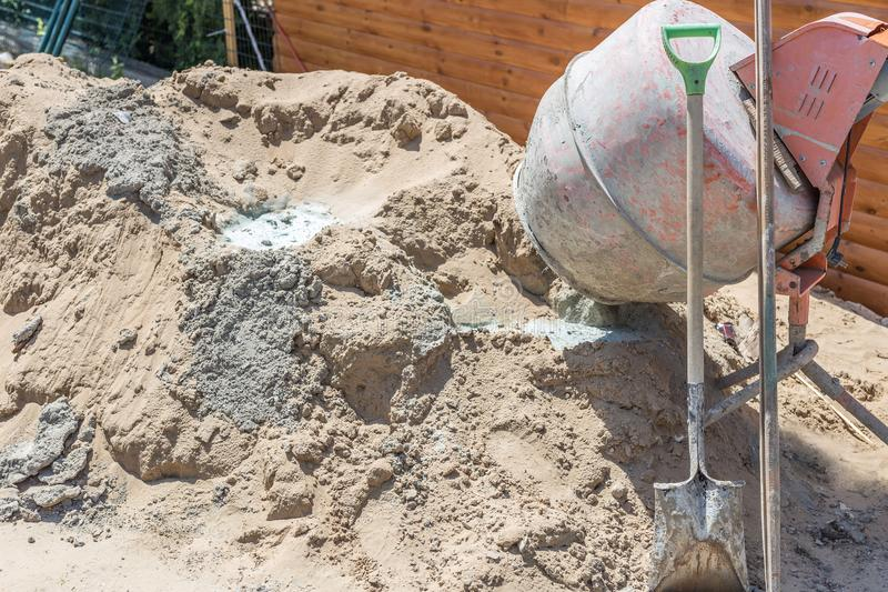 Old dirty concrete-mixer near sand heap at small construction site. Small portable cement mixing machine at home stock images