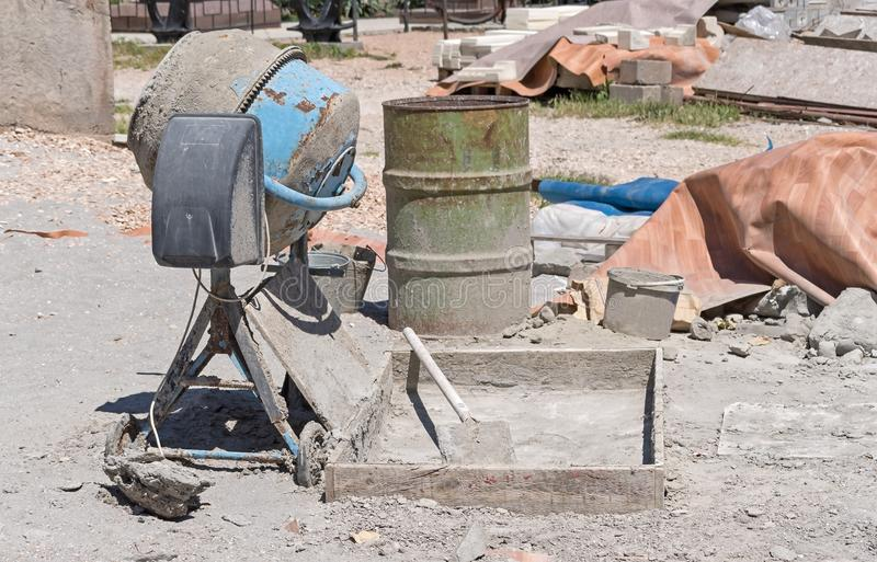 Old dirty concrete-mixer. At small construction site stock photography