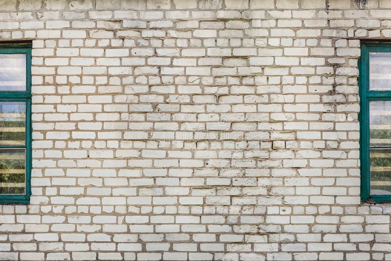 Old dirty cracked white brick wall with retro wooden windows by side. Grey textured background stock images