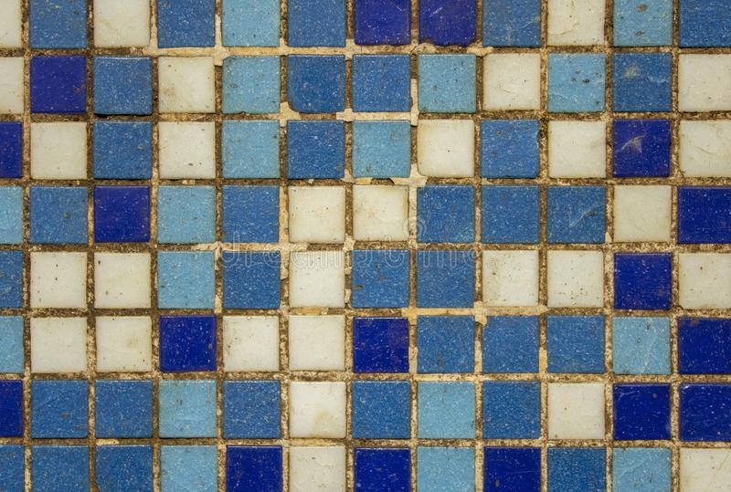 Old dirty damaged wall with white blue violet small square ceramic tiles. rough surface texture stock images