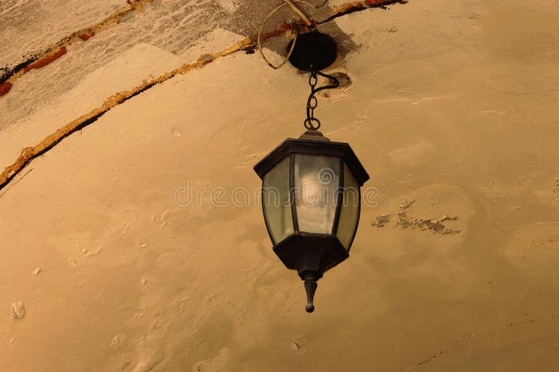 Old dirty dusty ceiling lamp on weathered plaster royalty free stock photo