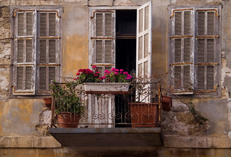 Old dirty facade flowers Jaffa Israel. An old neglected house with dirty facade and windows in Jaffa Israel stock photo