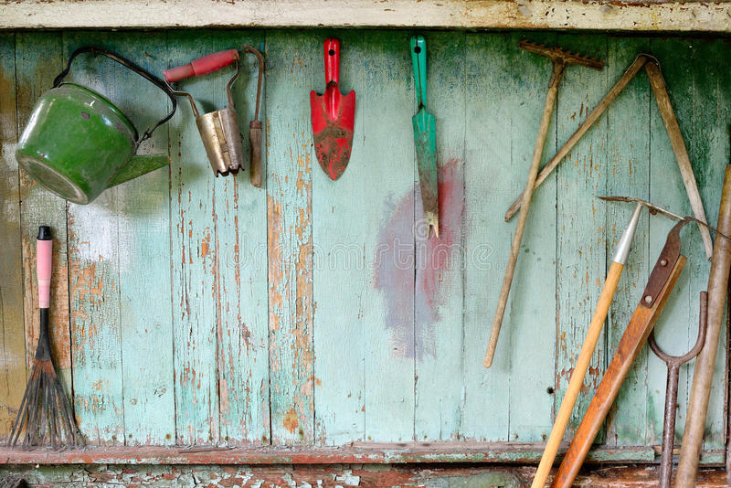 Old dirty farm gardening tools, spade, fork and rake on wooden wall royalty free stock images