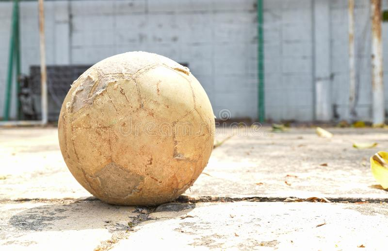 Dirty and old football. Old and dirty football on the ground of concrete football field royalty free stock photography