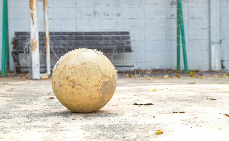 Old football. Old and dirty football on the ground of concrete football field royalty free stock images