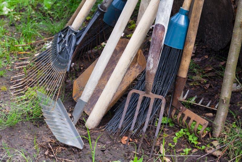 Old dirty garden tools. Cultivator, shovel, rake royalty free stock image