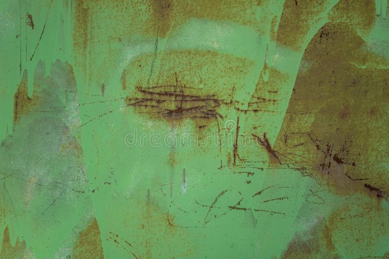 Old dirty green metal wall shield with stains of paint, scratches and dots of brown rust. rough surface texture royalty free stock photos