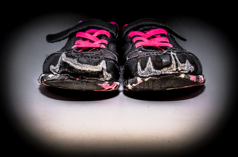 Old and dirty grey girl`s sneakers. On black background royalty free stock image