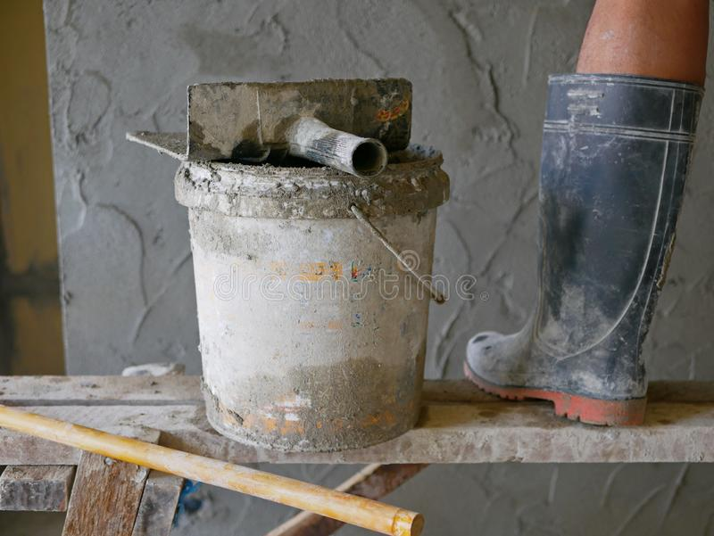 Old dirty grungy bucket and PVC plastic trowel on a wooden stand, being used for cement plastering by a construction worker stock photography