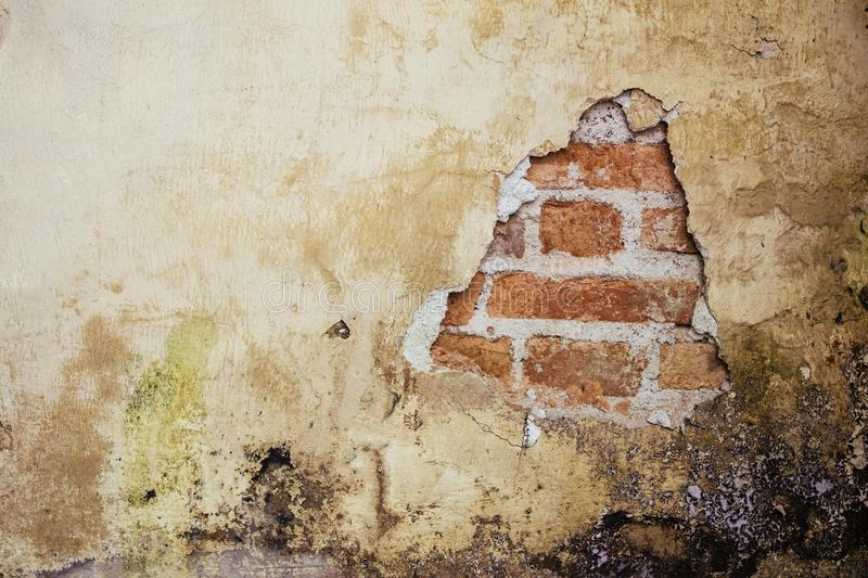 Old dirty and grungy plastered wall facade of an abandoned house with a hole showing the underlying red bricks royalty free stock photography