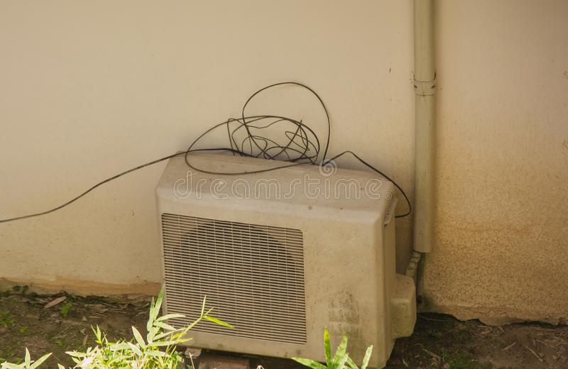 Old metal exterior fitted air conditioning unit staying on the ground needing maintenance. Old dirty metal exterior fitted air conditioning unit staying on the stock photo