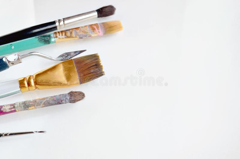 Old dirty painting brushes scattered on a white background. Painting brushes covered in oil paint and varnish. Background for a te royalty free stock photos
