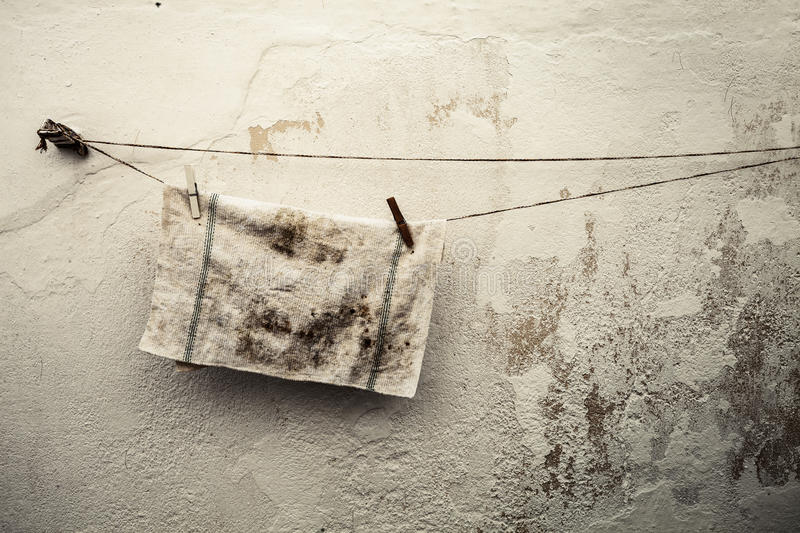 Old dirty rag hanging on a wire. Antique wall background. A dirty rag is hung on a nylon line to dry. Ancient grunge wall background royalty free stock photography
