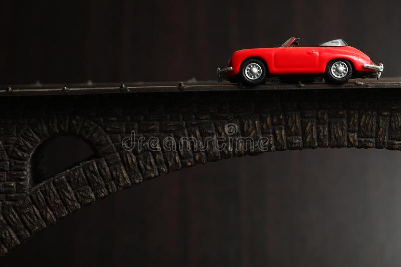Red car scene. The old and dirty red color miniature toy car put on the model toy bridge represent the transportation and vehicle concept related idea royalty free stock images