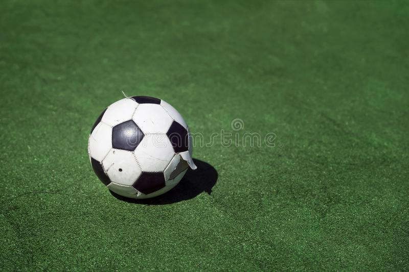 Old, dirty tattered soccer ball on background of green grass. Traditional classic black and white football ball on green royalty free stock images