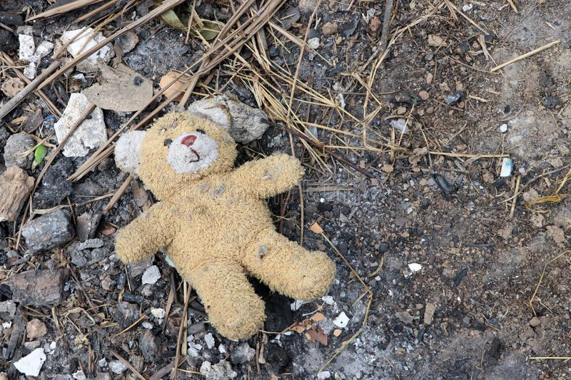 Old dirty teddy bear neglected on the ground soil. End of childhood. In Thailand stock photography