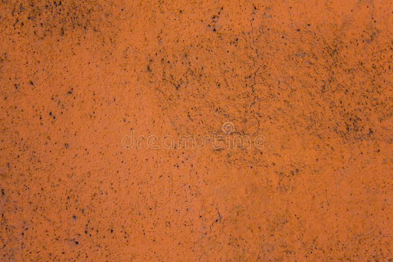 Old dirty terracotta orange surface porous granular wall with black dots and a large crack. rough texture royalty free stock photos