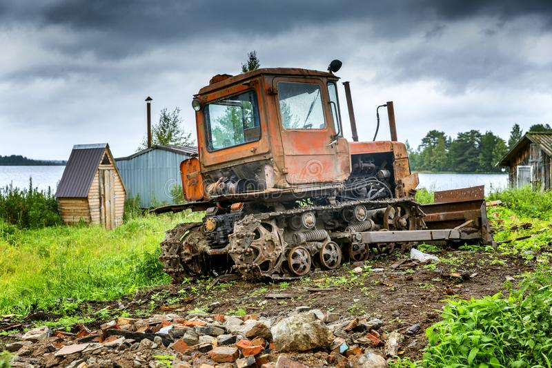 Old dirty tractor by the river in a rustic landscape royalty free stock image