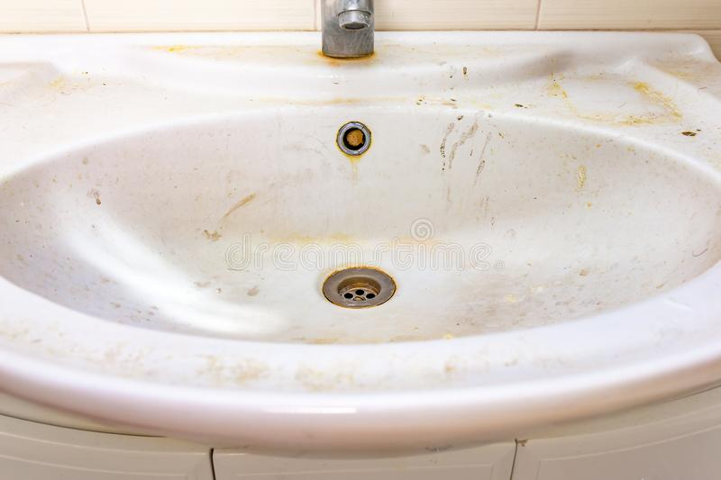 Old dirty washbasin with rust stains, limescale and soap stains in the bathroom with a faucet, water tap.  stock photo