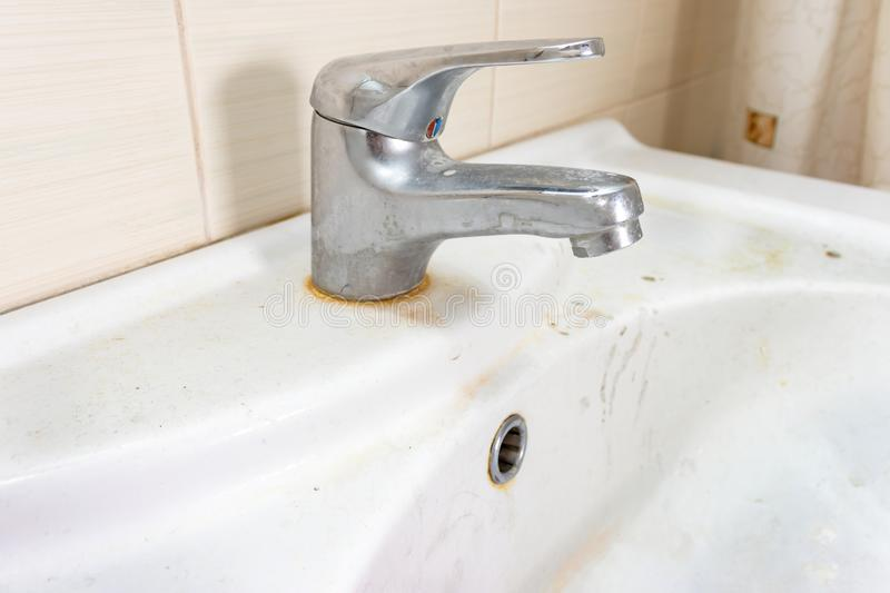 Old dirty washbasin with rust stains, limescale and soap stains in the bathroom with a faucet, water tap.  royalty free stock photo